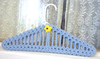 Handcrafted gifts one of our collectibles plastic hanger with blue hand crocheted cover with colored flower to dt1010fo